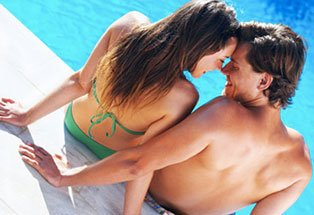 couple by swimming pool touching heads