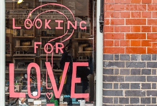 Photo of shop window with sign Looking For Love Reasons You Need to Date a Shorter Man Blog Matchmaking DDM